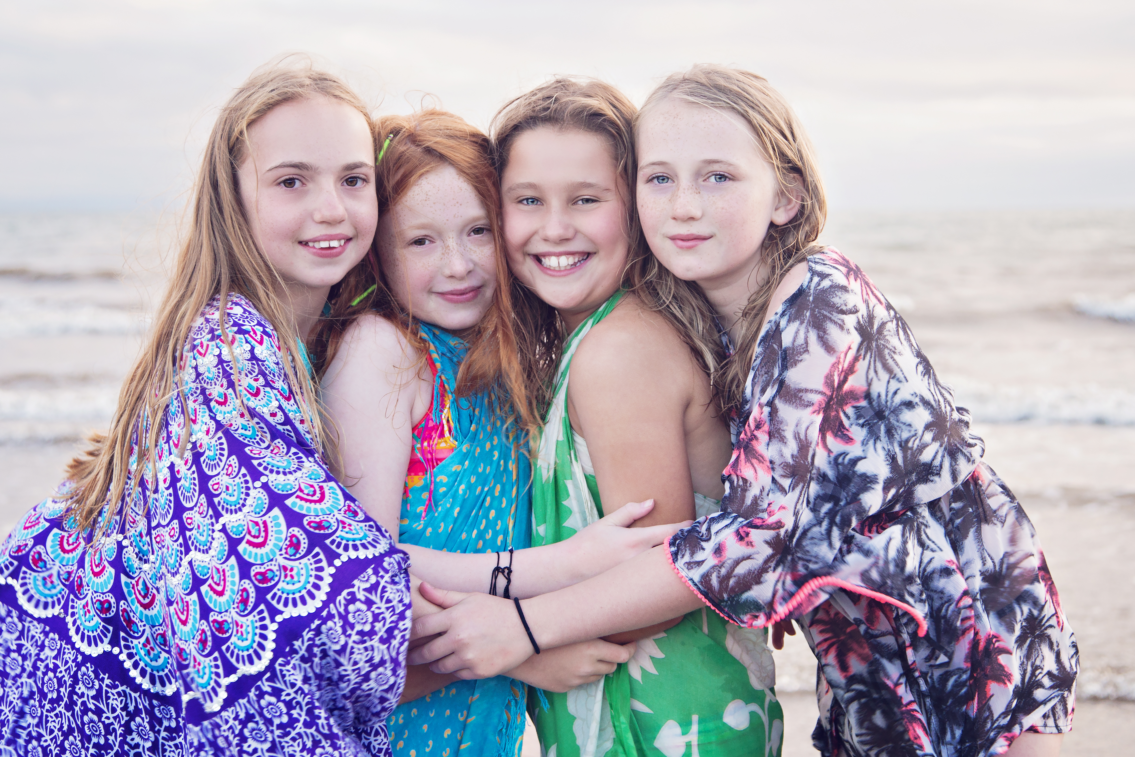 group of friends hugging on the beach