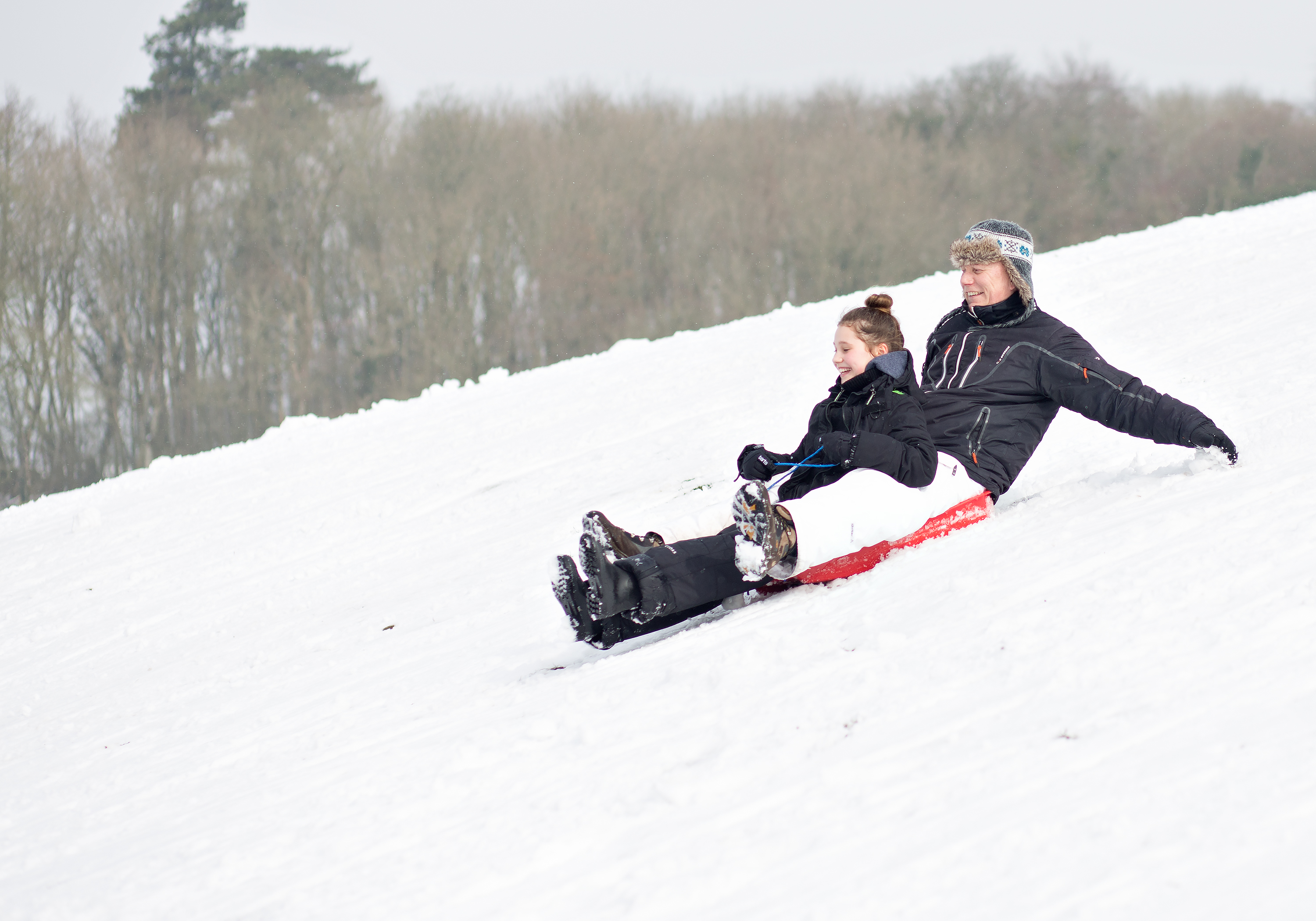girl and dad sledging