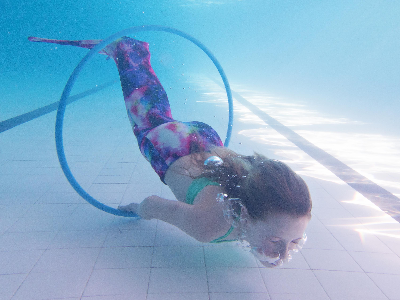 girl underwater in mermaid tail swimming through hoop