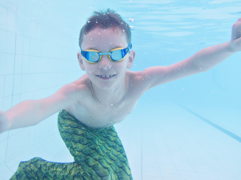 boy underwater in mermaid tail