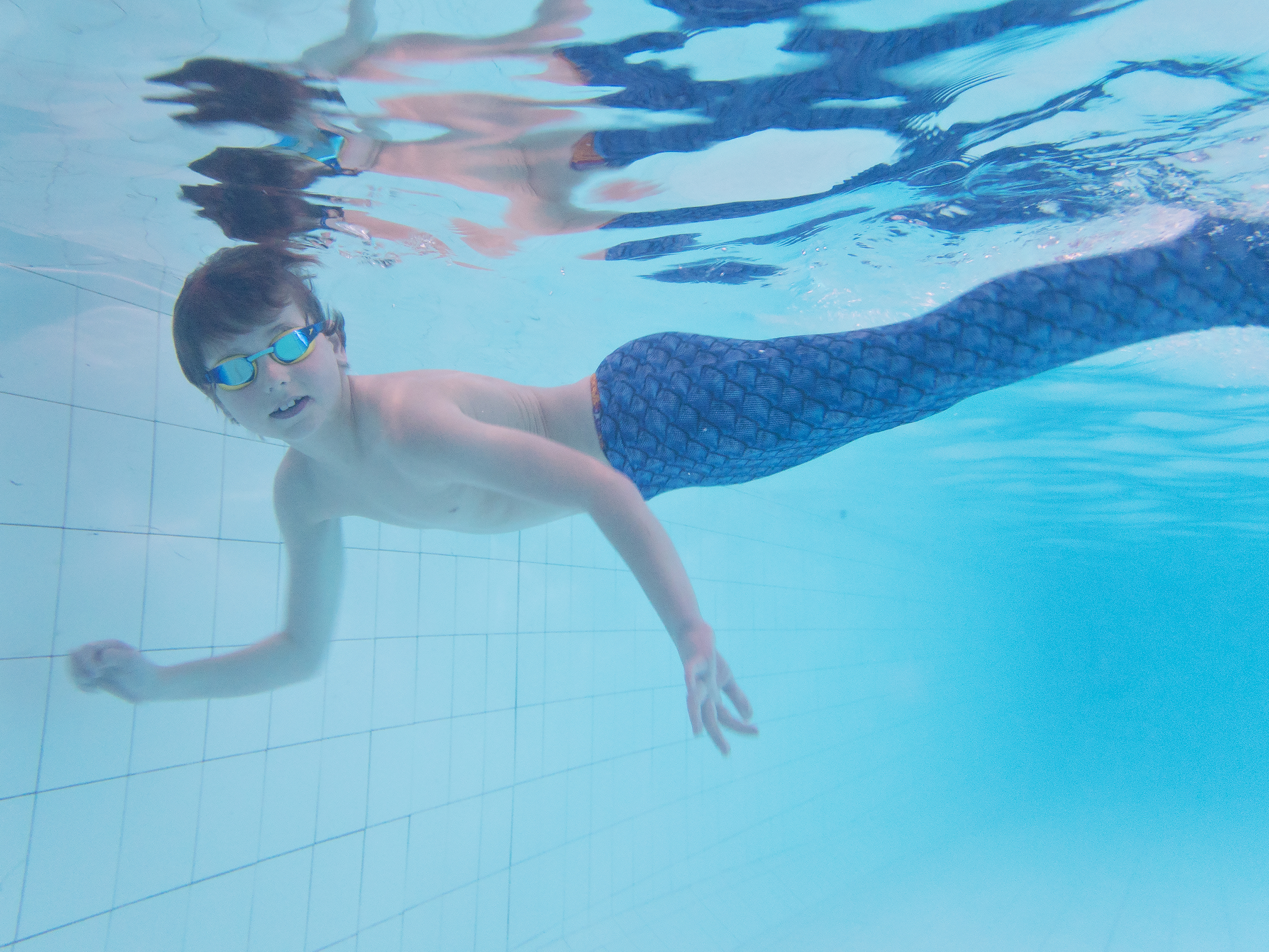 boy underwater in mermaid tail