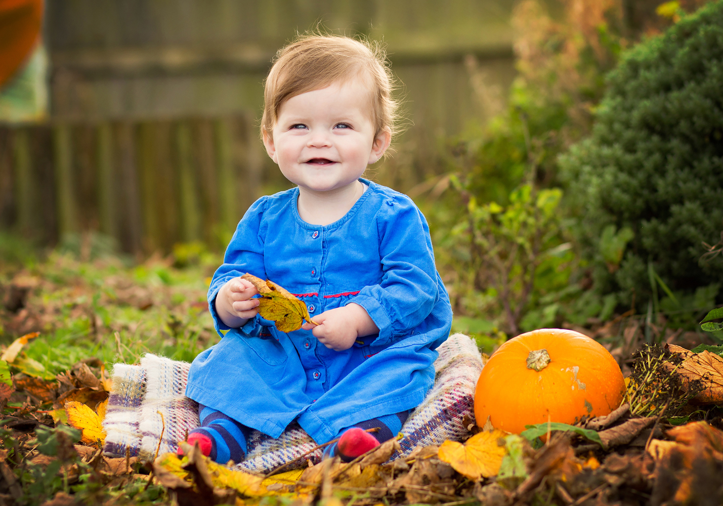 toddler smiling holding leaf