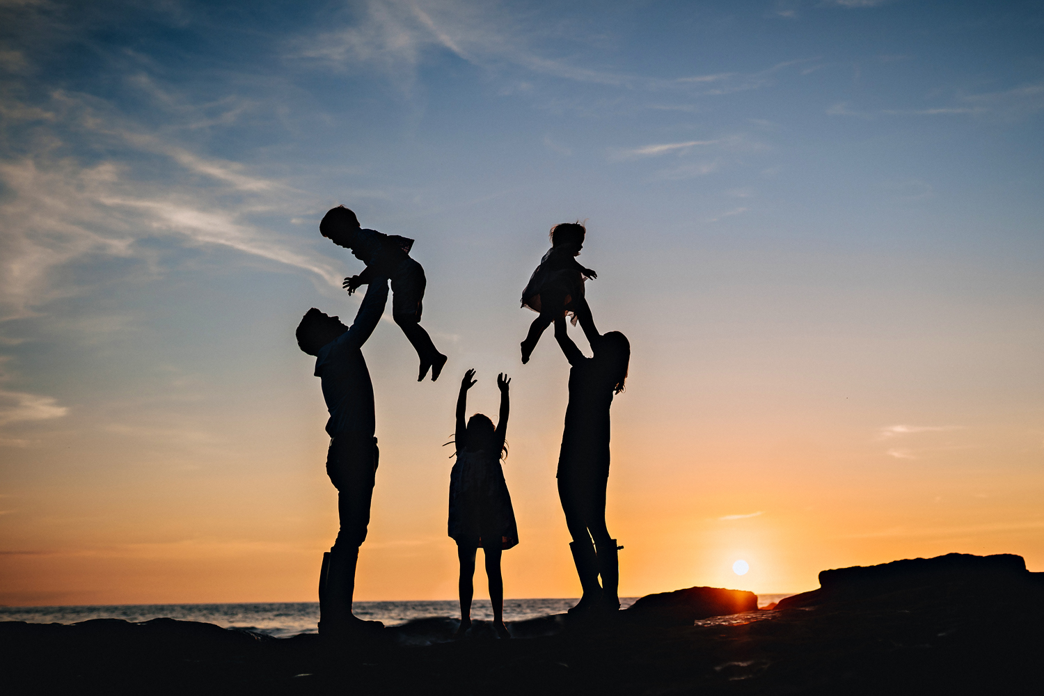 silhouette image of a family of 5 at sunset on the beach