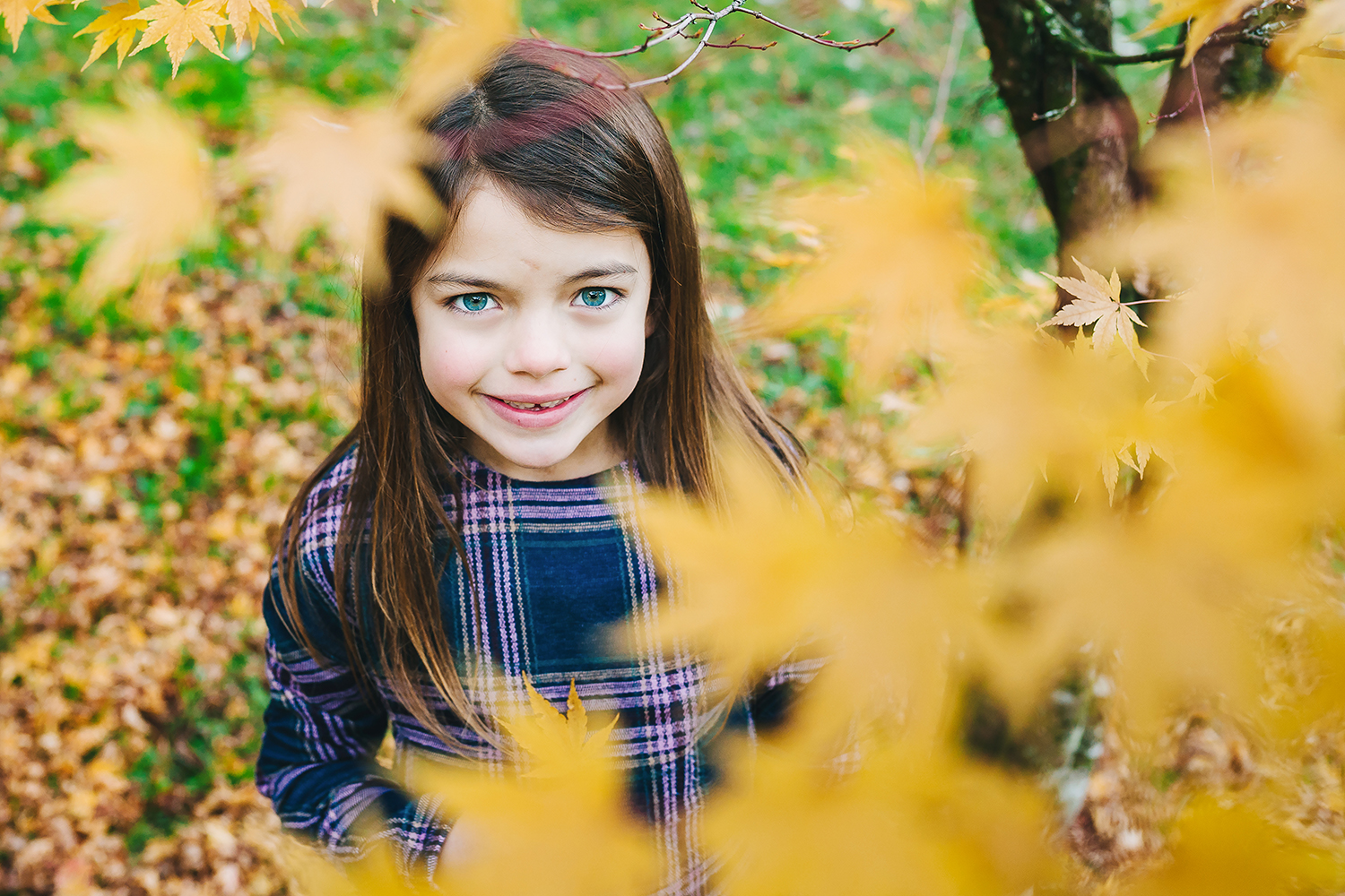 child smiling through leaves