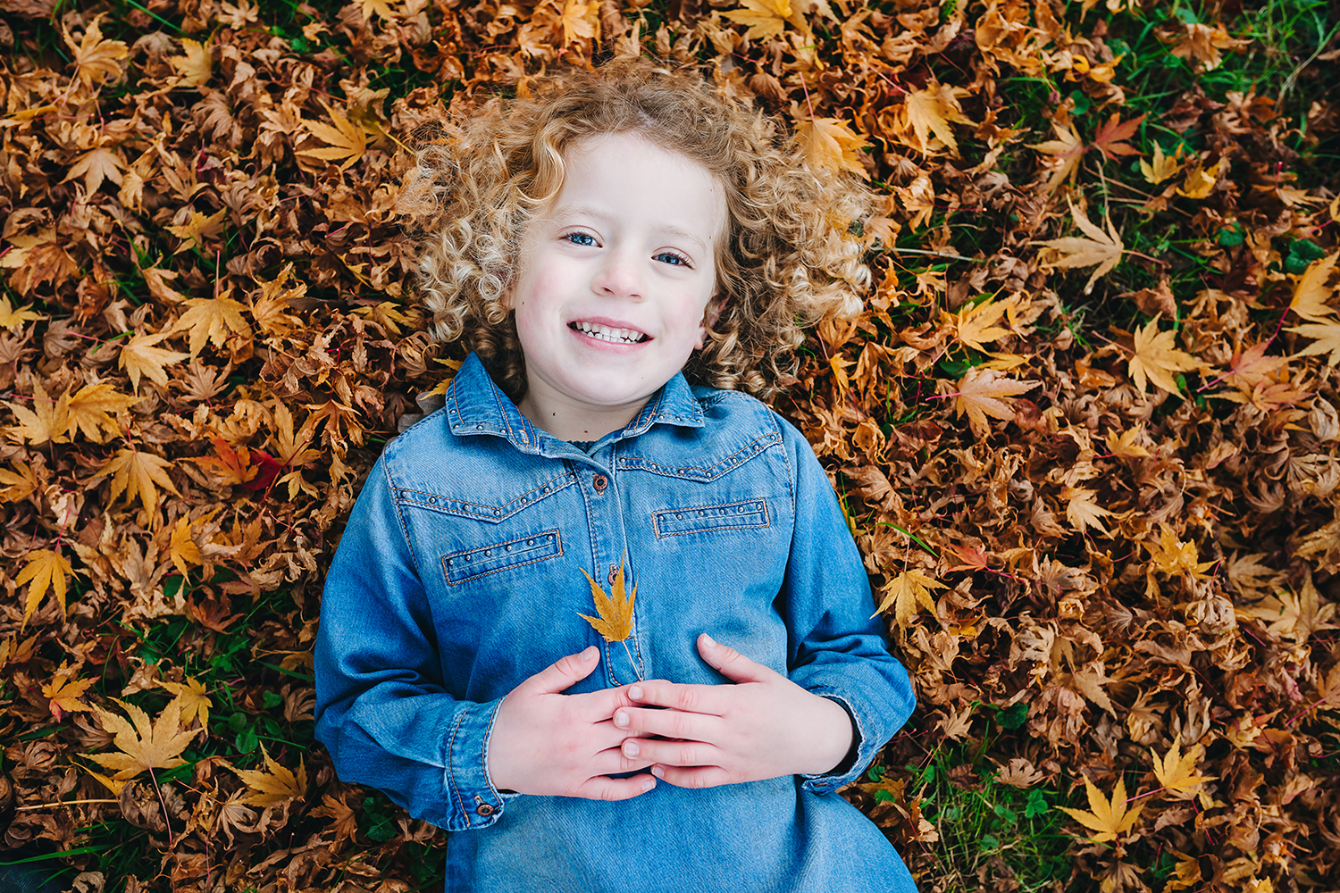 child smiling with leaf