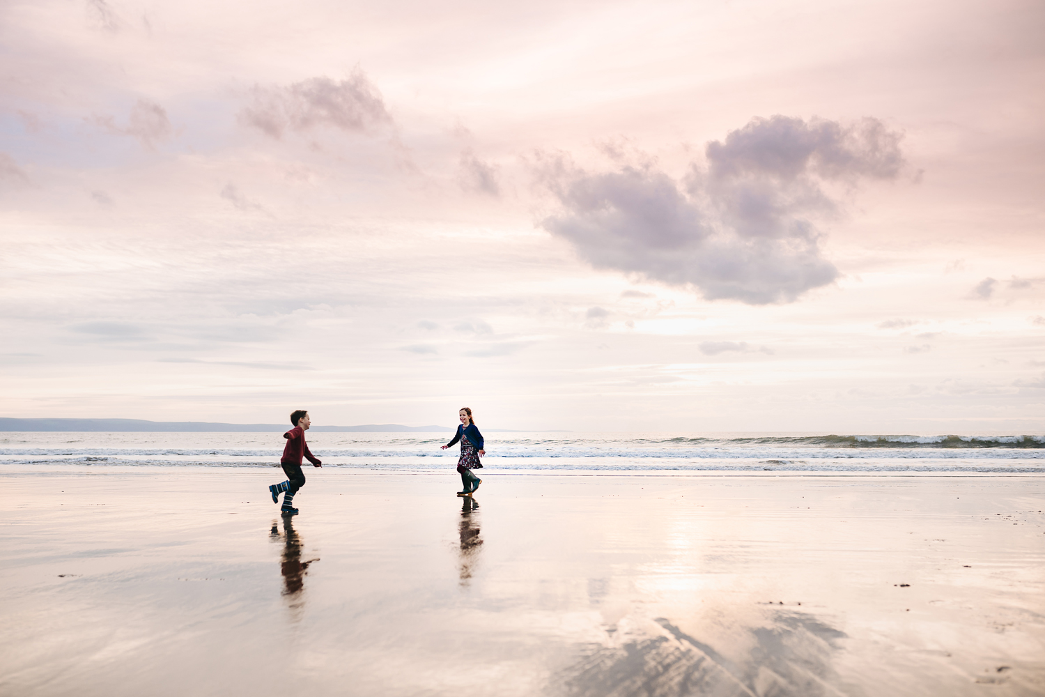 children playing on a beach at sunset