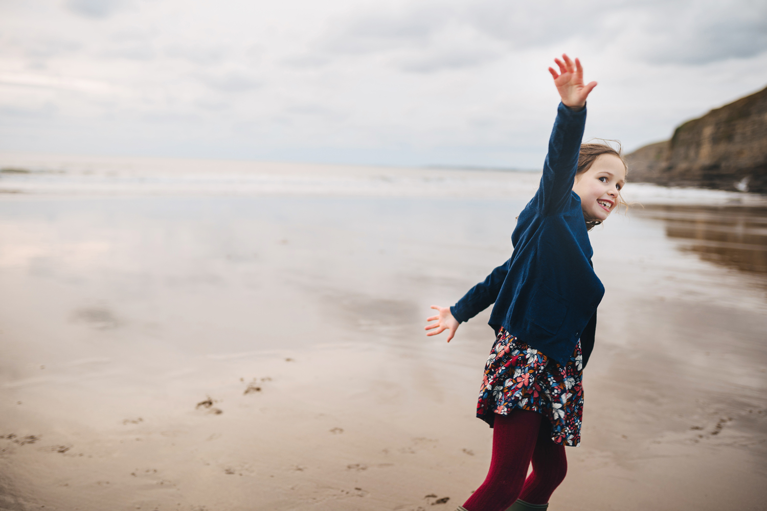 child running on the beach with outstretched arms
