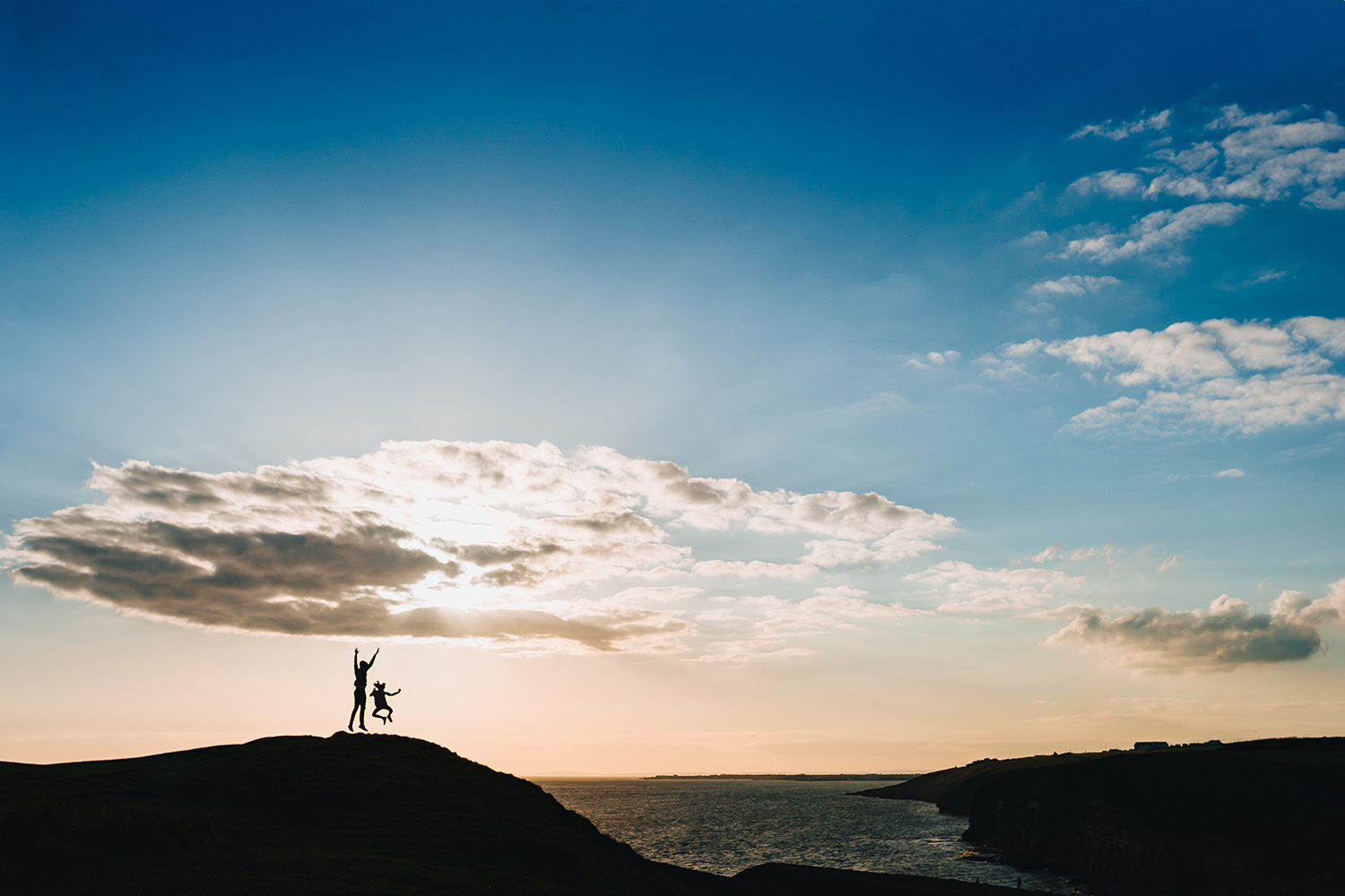 silhouette image of children jumping on a cliff top