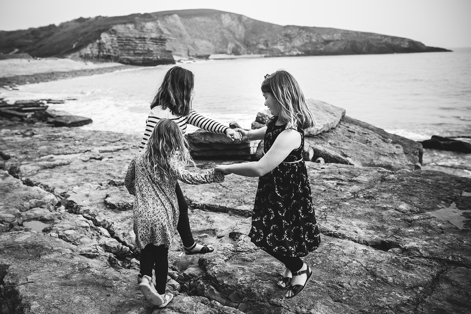 three girls holding hands on beach