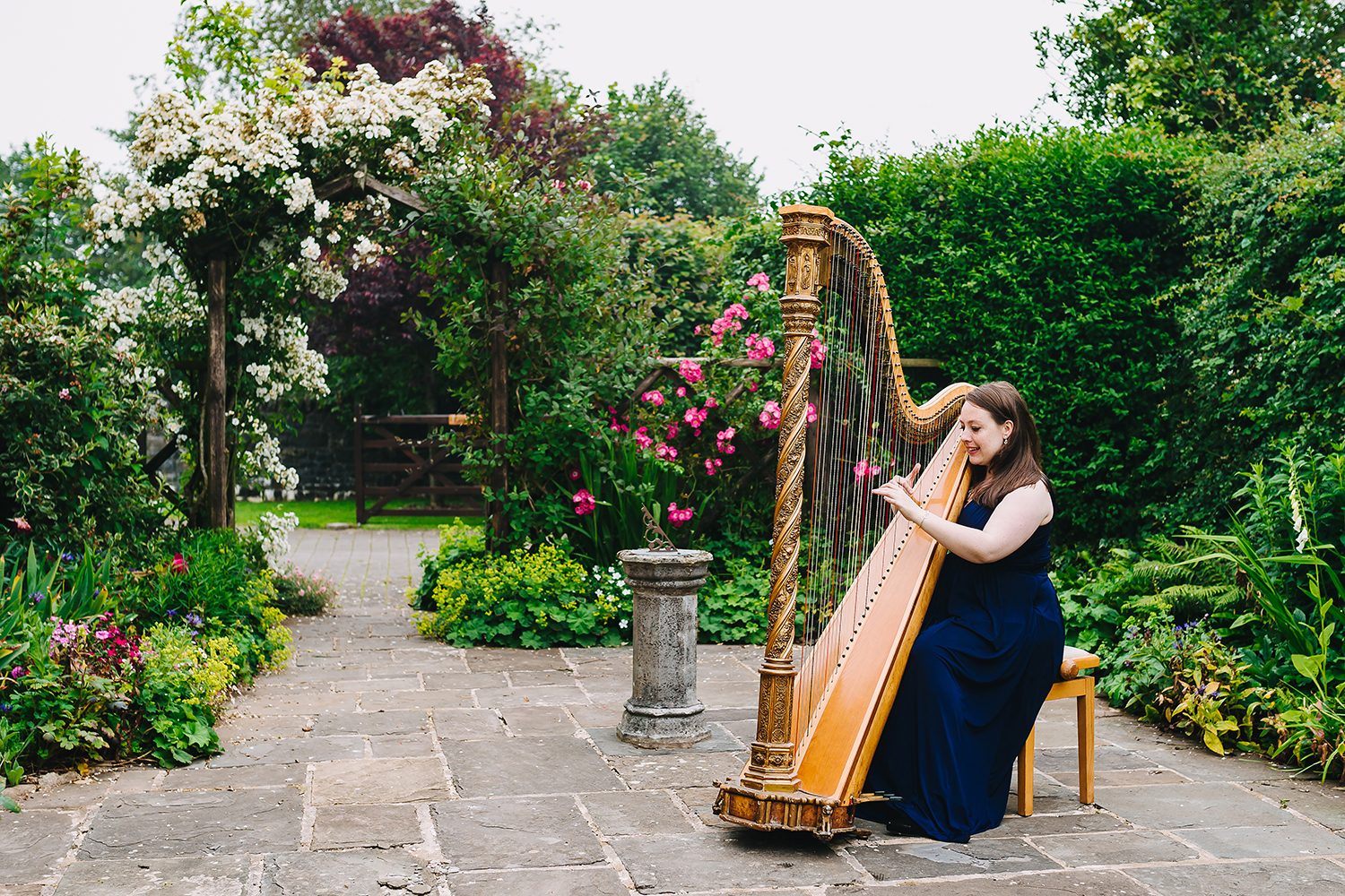 woman and harp in the garden