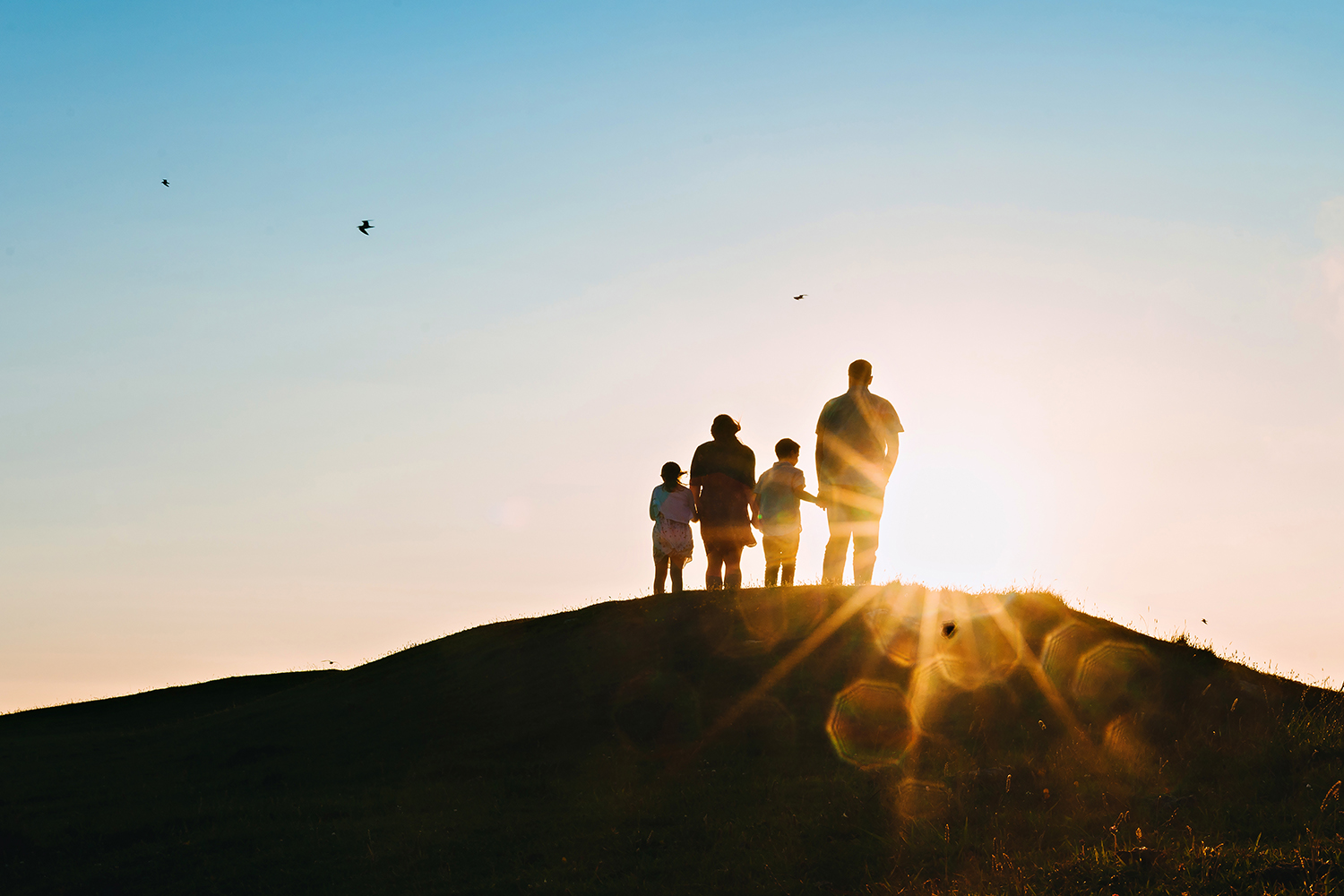 silhouette image of a family of 4 at sunset on the beach