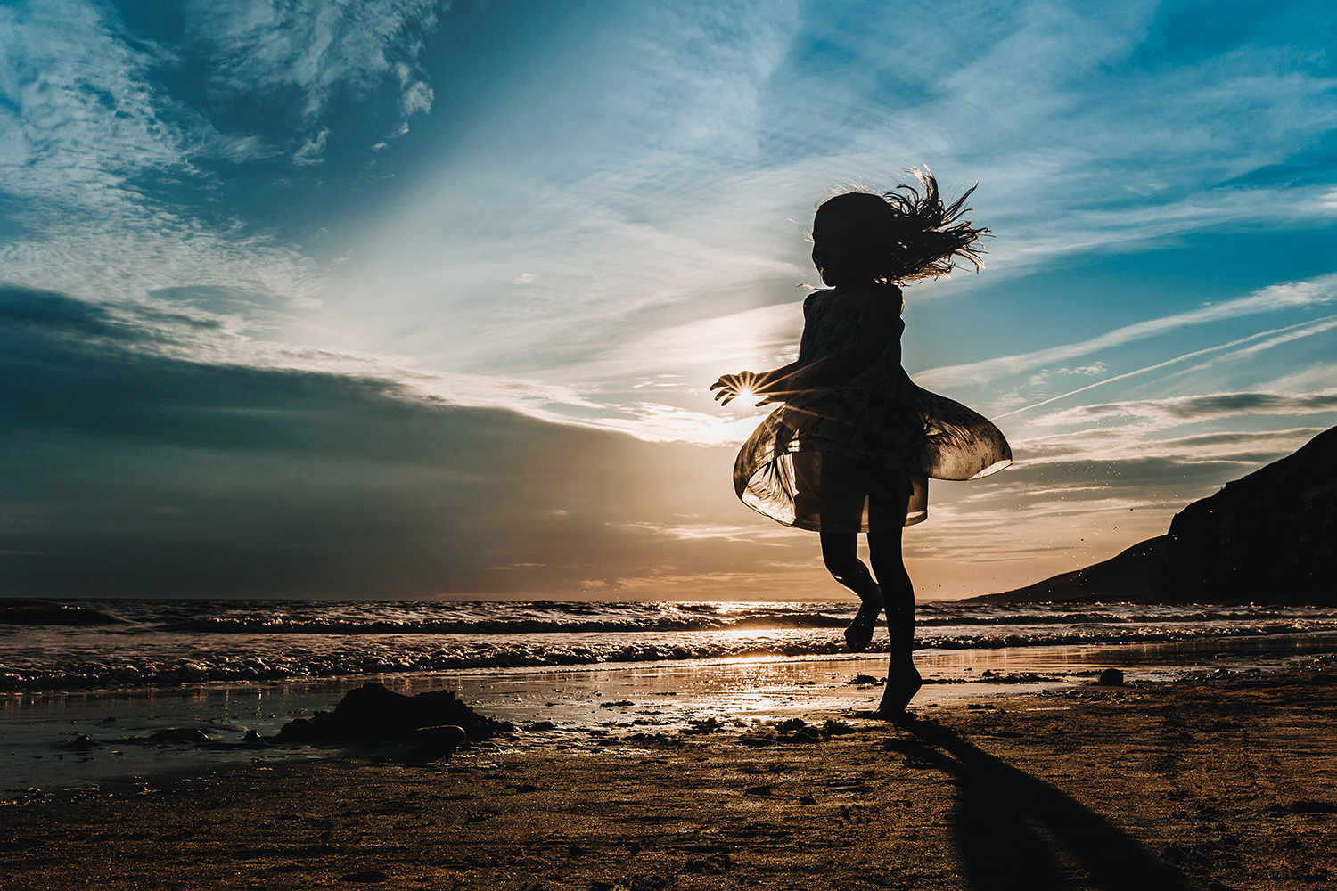 silhouette image of girl dancing on the beach at sunset