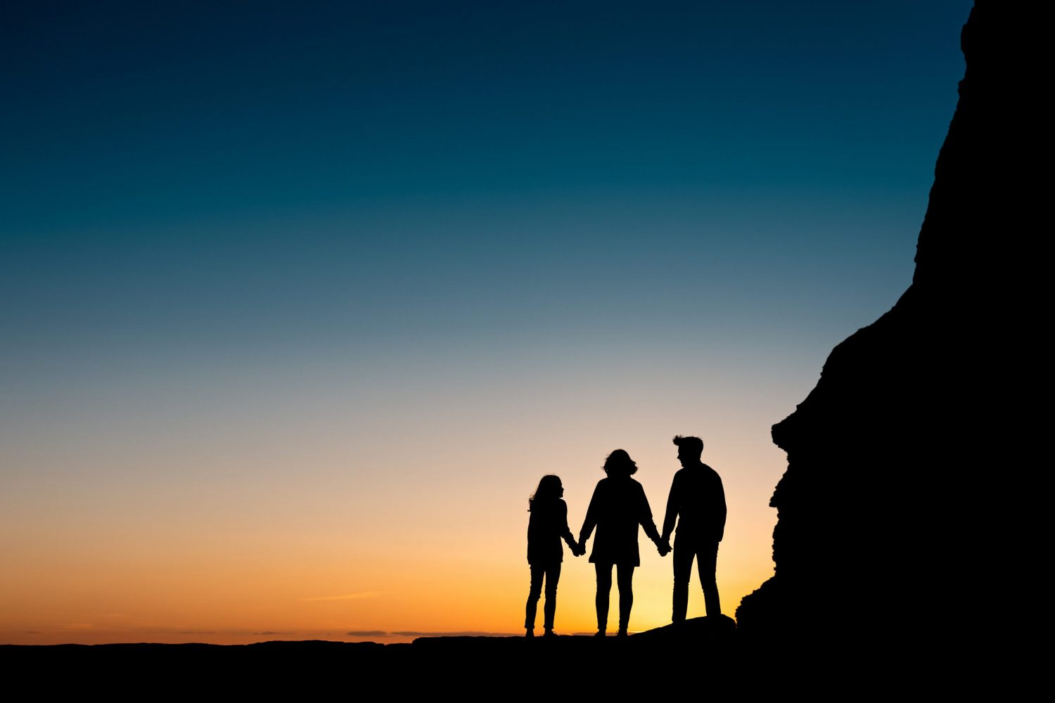 silhouette image of a family of 3 at sunset on the beach