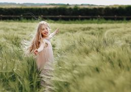 young girl running through a meadow